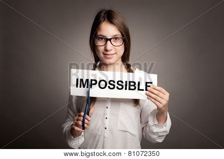 young girl cutting impossible word with scissors