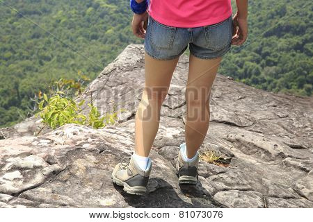 young woman hiker stand on mountain peak rock edge