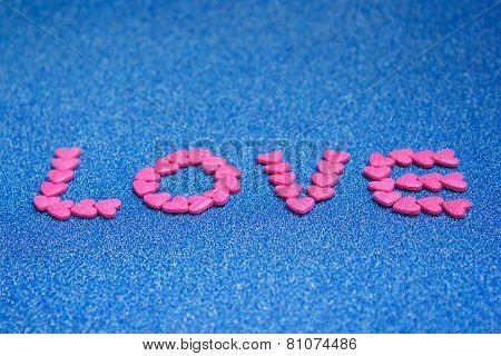 Candy Arrange As The Word Love On Blue Background..