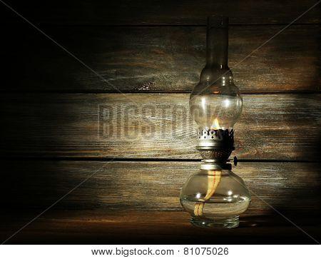 Kerosene lamp on rustic wooden planks background