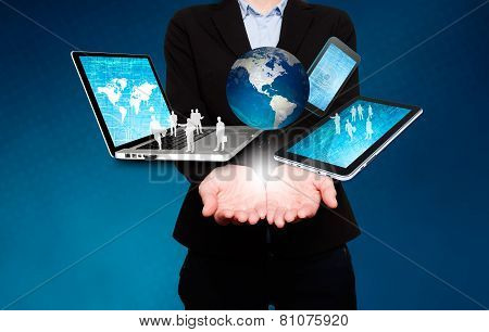 Businesswoman holds laptop, phone, tablet, globe in hands - Stock Image