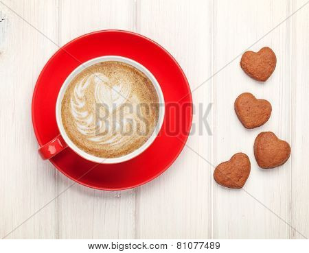 Valentines day heart shaped cookies and red coffee cup. View from above over white wooden table