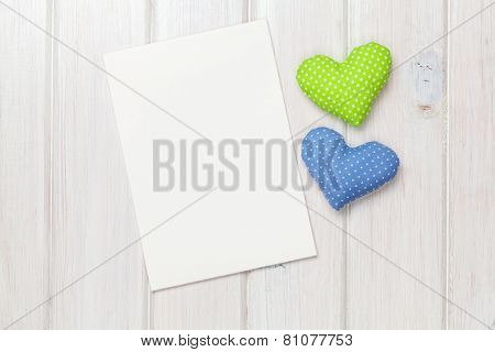 Photo frame or greeting card and handmaded valentines day toy hearts over white wooden background