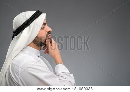 Arab man thinking hard with hand on his face