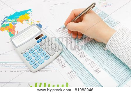 Male Holding Silver Ball Pen And Trying To Fill Out Us 1040 Tax Form