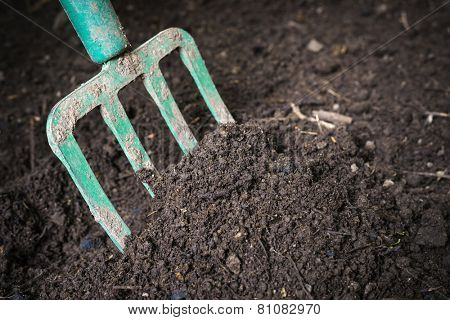 Garden fork turning  black composted soil in compost bin ready for gardening, close up.
