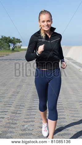 Fit blonde jogging on the pier on a sunny day