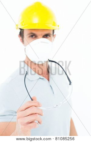 Portrait of confident worker wearing mask and hardhat while holding protective glasses over white background