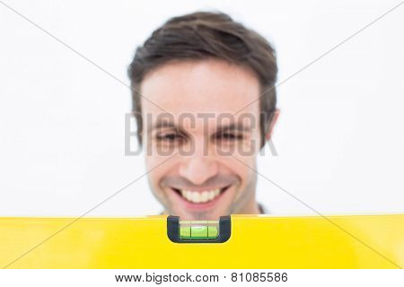 Happy repairman looking at spirit level over white background