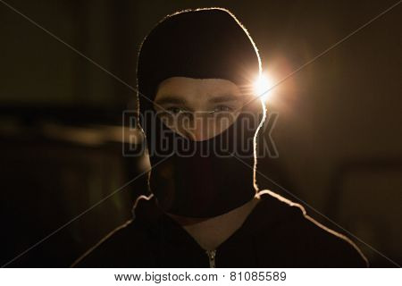 Criminal in balaclava looking at camera in a shadowy setting