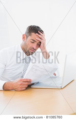 Confused businessman looking at his paper in his office