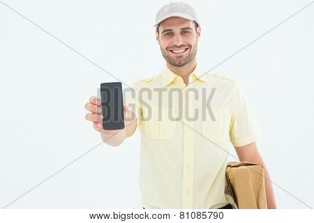 Portrait of handsome delivery man showing mobile phone on white background