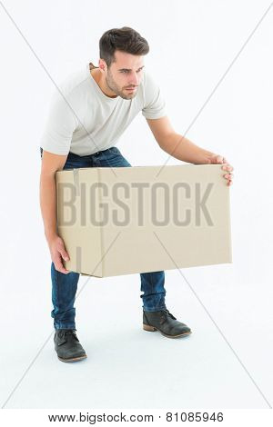 Full length of courier man picking up cardboard box on white background