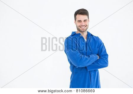 Portrait of smiling young male machanic standing arms crossed on white background