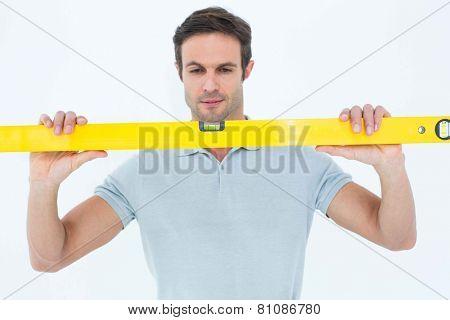 Handsome repairman holding spirit level over white background