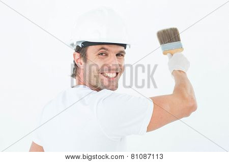Rear view portrait of happy man using paintbrush on white background