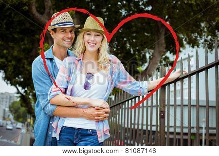 Hip young couple smiling at camera by railings against heart