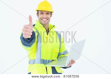Portrait of male architect in reflective clothing with laptop gesturing thumbs up over white background