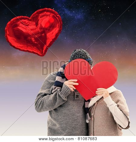 Happy mature couple in winter clothes holding red heart against aurora in night sky
