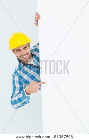 Portrait of confident repairman pointing at blank billboard on white background