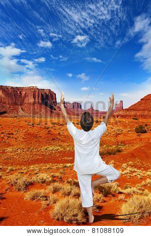 Navajo Reservation in the US. Red Desert and freestanding sandstone cliffs. Woman in white doing yoga