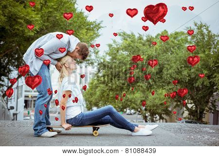Hip young blonde sitting on skateboard with boyfriend kissing forehead against red heart balloons floating