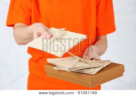 Courier with parcel box and letters close-up