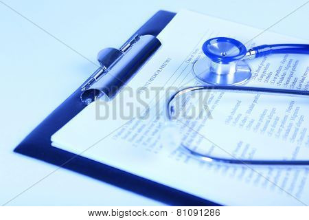 Medical history on clipboard with stethoscope on light background