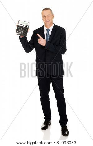 Mature businessman pointing on calculator.