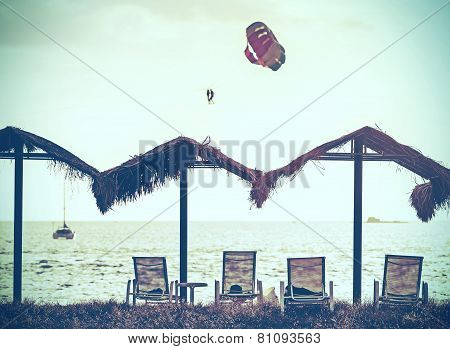 Retro Vintage Filtered Picture Of Beach And Paragliders At Sunset.