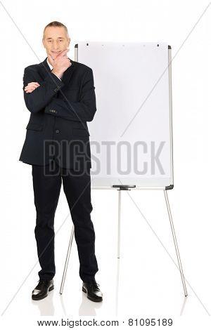 Mature businessman with marker standing near flip chart.