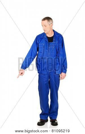 Mature repairman in uniform pointing down.