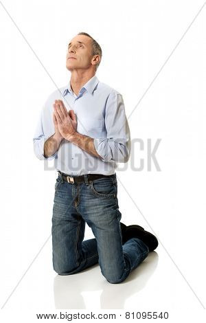 Man kneeling and praying to God.