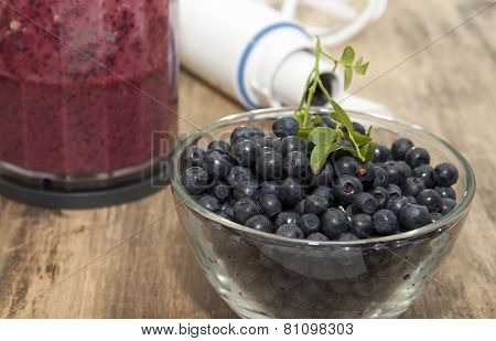 Blueberries In A Glass Bowl, A Blender And A Glass With A Smoothie Of Blueberries.