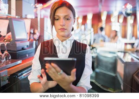 Focused barmaid using touchscreen till in a bar