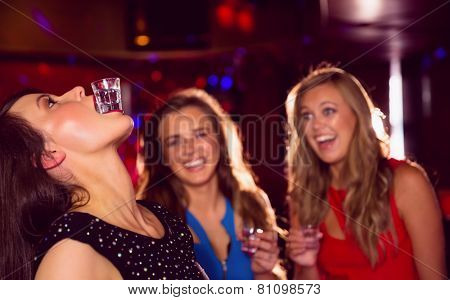 Pretty friends drinking shots together at the nightclub