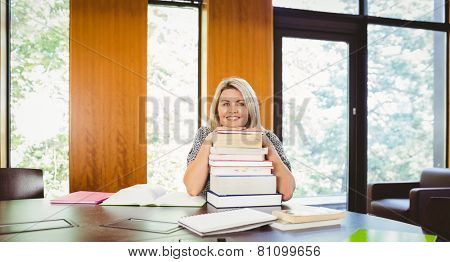 Smiling blonde mature student with stack of books in library