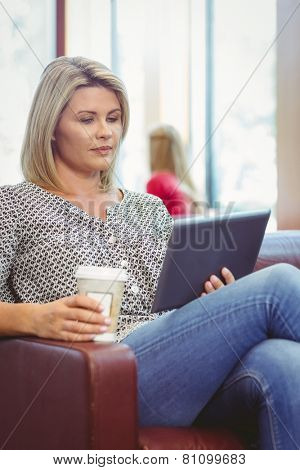 Woman using digital tablet and holding disposable cup in library