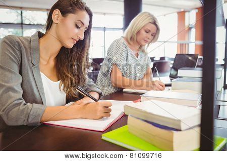 Matures females students writing notes at desk in library