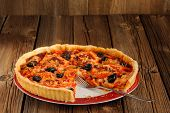 image of tarts  - Tomato tart with olives and red pepper with space old wood background horizontal  - JPG