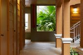 foto of florida-orange  - Looking down an outside hallway or walkway in naples florida surrounded towards palms in the rain - JPG