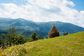 foto of haystack  - Haystack and wooden cart against the summer landscape in the Ukrainian Carpathians - JPG