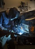 image of welding  - Man wearing welding helmet and welding the bumper of a vehicle - JPG