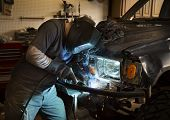picture of welding  - Man wearing welding helmet and welding the bumper of a vehicle - JPG