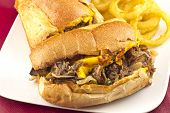 stock photo of cheesesteak  - A messy Philly Cheesesteak with onions peppers and mushrooms onion rings on the side - JPG