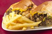 image of cheesesteak  - A messy Philly Cheesesteak with onions peppers and mushrooms fries on the side - JPG