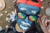 image of crazy face  - crazy man with blue face wearing rainbow glasses - JPG