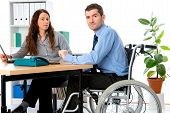 image of workplace accident  - man in wheelchair and his is female colleague working in the office - JPG