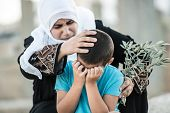 stock photo of arabic woman  - Arabic Muslim Middle Eastern woman with olive branch and son crying - JPG