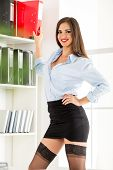 foto of mini-skirt  - Pretty young business woman in a short skirt standing in front of shelves with binders and with a smile looking at the camera.